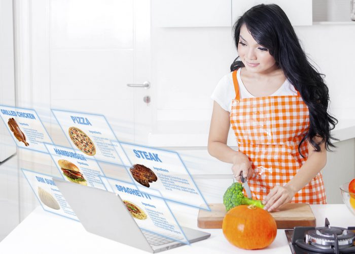 Picture of pretty woman wearing apron while cutting broccoli and looking at a virtual food recipes on laptop in the kitchen